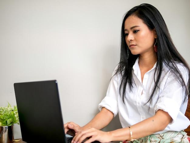 Femme d'affaires asiatique attrayante belle dans l'espace de co-travail à la recherche à l'écran d'ordinateur portable pour