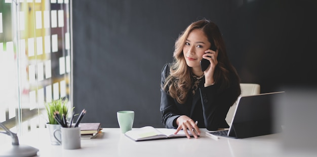 Femme d'affaires asiatique attrayante souriante et à la recherche