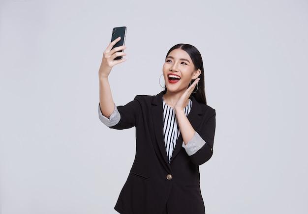 Une femme d'affaires asiatique au visage heureux et amical sourit en costume formel avec son smartphone a un appel vidéo sur fond blanc tourné en studio.
