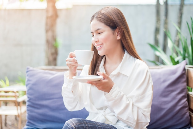 Femme d'affaires asiatique boit du café le matin au café