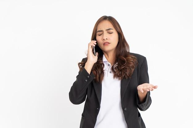 Femme d'affaires asiatique confondue avec un geste en détresse lors d'un appel téléphonique