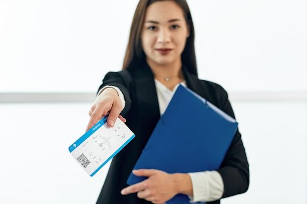 Femme d'affaires asiatique donnant des billets en attente de départ à l'aéroport