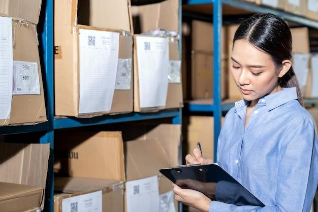 Femme d'affaires asiatique écrit pour contrôle d'inventaire
