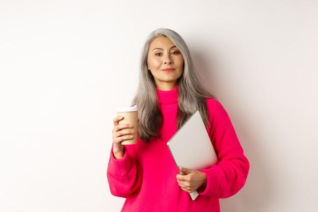 Femme d'affaires asiatique élégante buvant du café et tenant un ordinateur portable à l'air confiant et suffisant devant ...