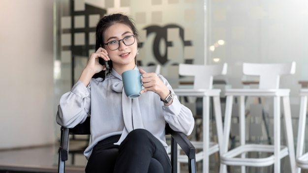 Femme d'affaires asiatique est heureuse de boire du café et de parler au téléphone pendant votre temps libre au bureau.