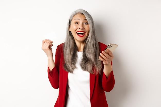 Femme d'affaires asiatique excitée en blazer rouge, tenant une carte de crédit en plastique et un smartphone, souriant heureux à la caméra, debout sur fond blanc.