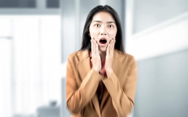 Femme d'affaires asiatique avec expression choquée sur la salle de bureau