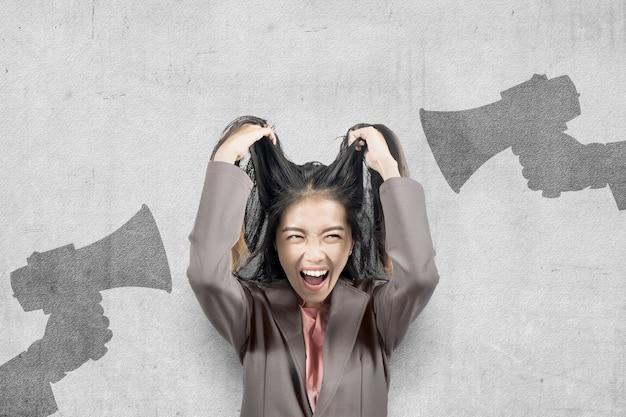 Femme d'affaires asiatique avec une expression stressée avec fond de mur gris