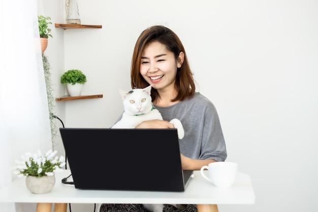 Femme d'affaires asiatique heureuse travaille de bureau à domicile avec chat