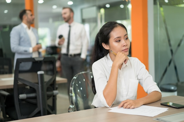 Femme d'affaires asiatique jolie songeuse assis au bureau dans le bureau