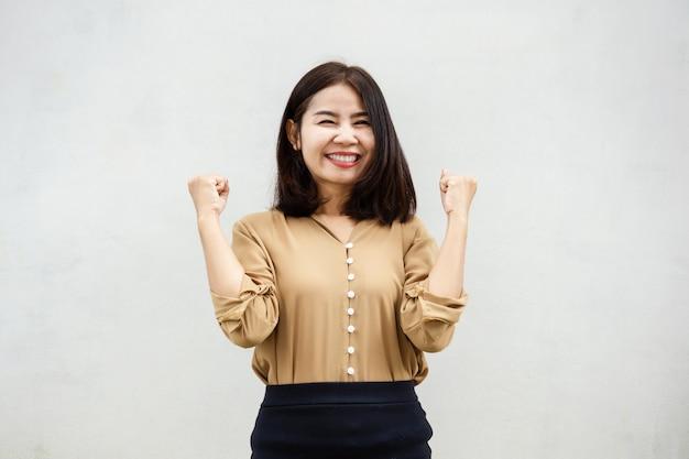 Femme d'affaires asiatique joyeuse souriante contre le mur gris