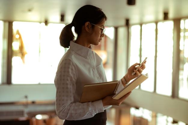 Femme d'affaires asiatique occupée porte des lunettes à l'aide d'un message texte lu tout en lisant un rapport financier