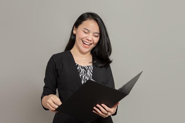 Femme d'affaires asiatique riant tout en tenant le dossier