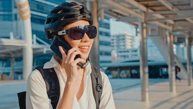 Femme d'affaires asiatique avec sac à dos à l'aide de téléphone portable dans la rue de la ville aller travailler au bureau.