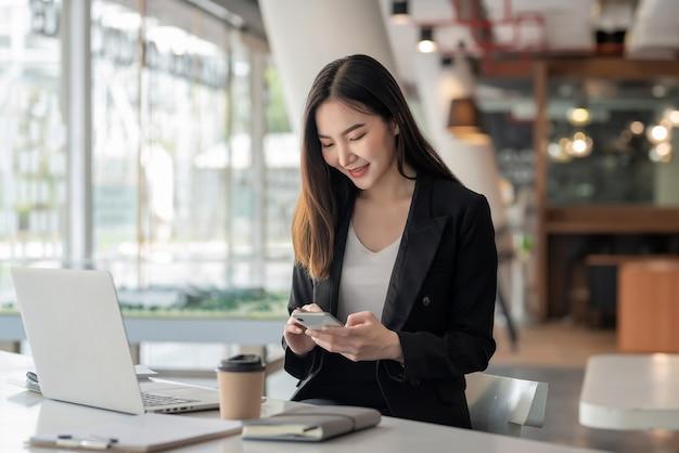 Une femme d'affaires asiatique se détend et aime jouer au téléphone portable au bureau.