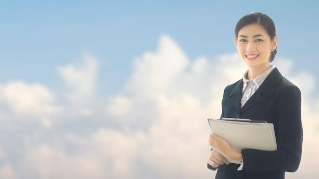 Femme d'affaires asiatique se dresse avec un fichier papier de présentation et d'affichage confiant.
