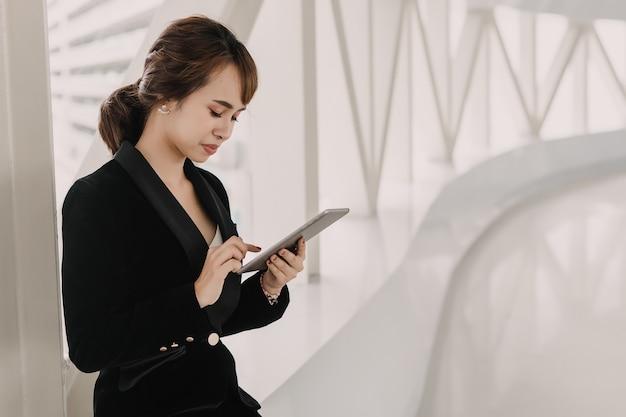 Femme d'affaires asiatique sérieuse tenant sur son téléphone portable