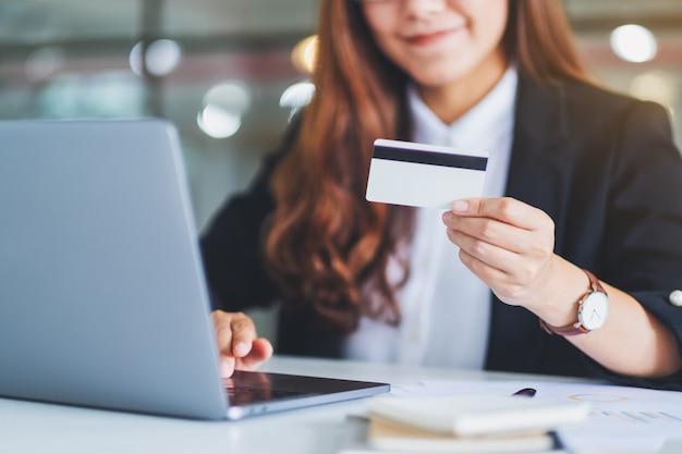 Une femme d'affaires asiatique tenant des cartes de crédit tout en utilisant un ordinateur portable au bureau