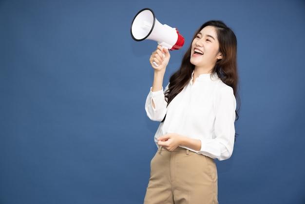 Femme d'affaires asiatique tenant un mégaphone isolé sur une surface bleue.