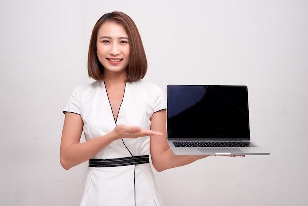 Femme d'affaires asiatique tenant un ordinateur portable sur blanc