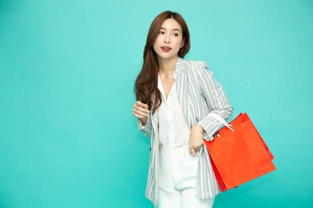 Femme d'affaires asiatique tenant des sacs à provisions rouges avec festival du nouvel an chinois isolé sur fond vert