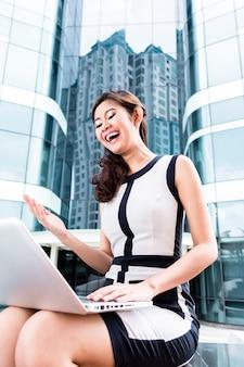 Femme d'affaires asiatique travaillant sur un ordinateur portable en face du bâtiment de la tour