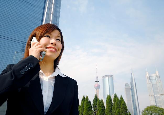 Femme d'affaires asiatique travaillant par les gratte-ciels.