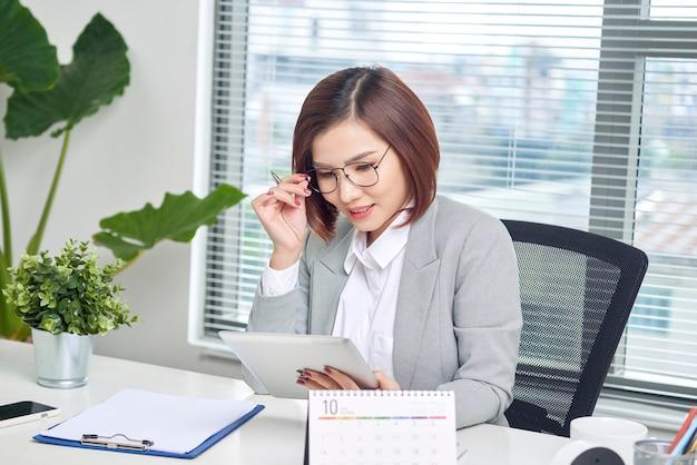 Femme d'affaires asiatique travaillant avec une tablette tactile au bureau.