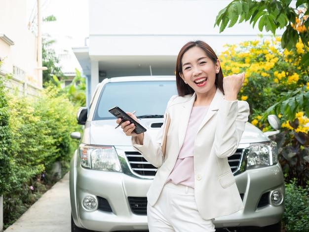 Femme d'affaires asiatique utilisant un téléphone intelligent contre une voiture.