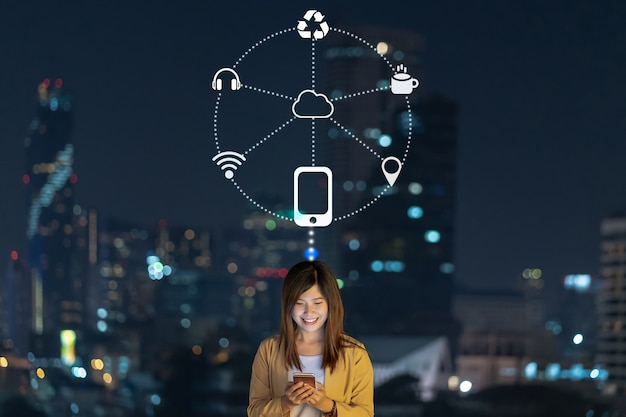 Femme d'affaires asiatique utilisant un téléphone mobile intelligent avec action de sourire pour faire fonctionner diverses icônes