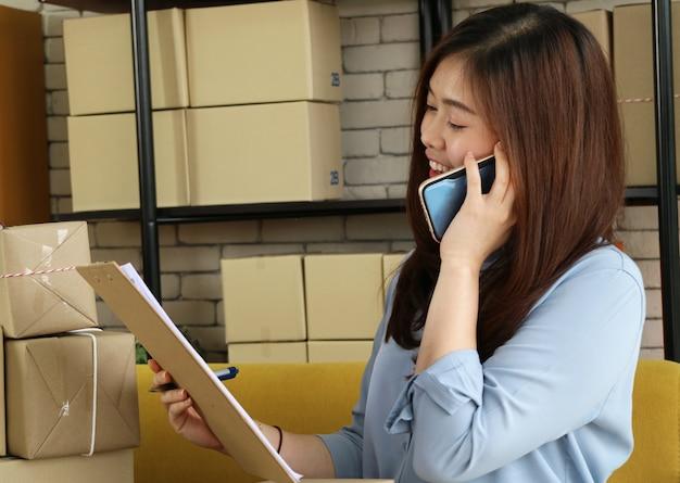 Femme d'affaires asiatique utilise un appel de smartphone au client pour la commande.