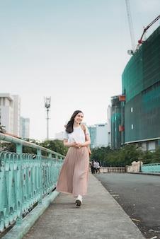 Femme d'affaires asiatique voyageant, debout près du pont de balustrade, lisant un livre sur fond de ville.