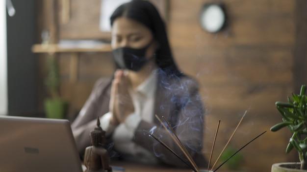 Femme d'affaires asiatiques priant au bureau