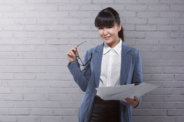 Femme d'affaires asiatiques tenant un papier et des lunettes