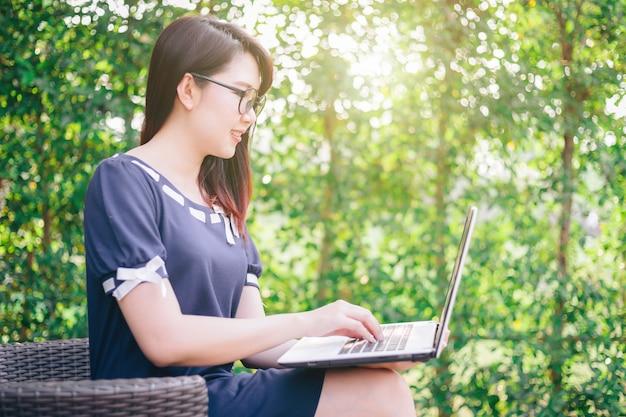 Femme d'affaires asiatiques travaillant avec un ordinateur portable sur le bureau en plein air.