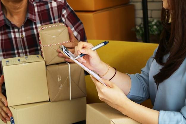 Femme d'affaires asiatiques vérifiant la liste des colis à livrer au client.