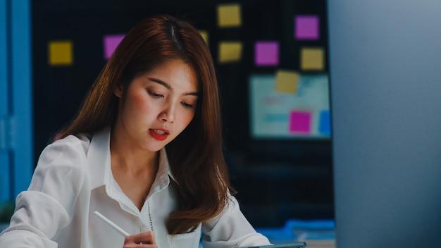 Femme d'affaires d'asie à l'aide d'un ordinateur parler à des collègues du plan en appel vidéo tout en travaillant à domicile au salon la nuit. auto-isolement, distanciation sociale, mise en quarantaine pour la prévention des coronavirus.