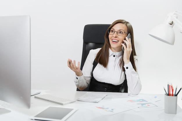 Femme d'affaires assez souriante en costume assise au bureau, travaillant sur un ordinateur contemporain avec un document dans un bureau léger, parlant au téléphone portable, menant une conversation agréable