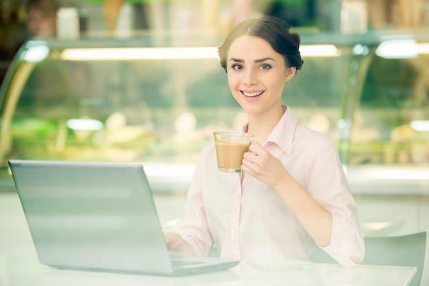 Femme d'affaires assis dans un café urbain et à l'aide d'un ordinateur portable.