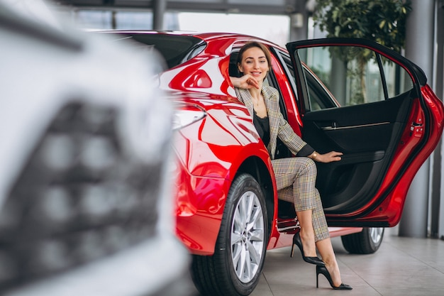 Femme d'affaires assis dans une voiture rouge