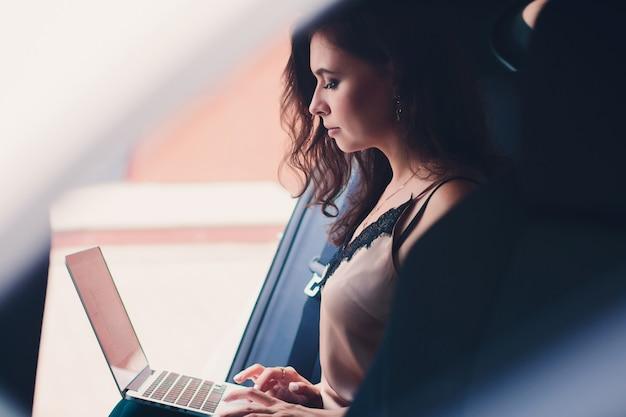 Femme d'affaires assis sur le siège arrière d'une voiture d'élite tenant un ordinateur portable.