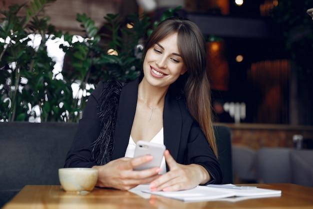 Femme d'affaires assis à la table dans un café et travaillant