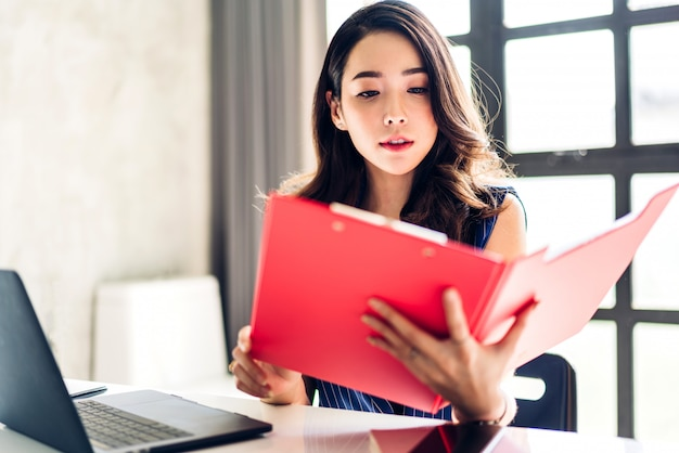 Femme d'affaires assis et travaillant avec un ordinateur portable. hommes d'affaires créatifs, planification dans son poste de travail au loft de travail moderne
