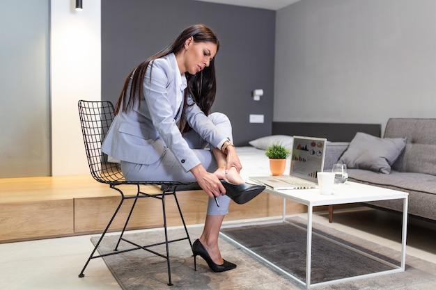 Femme d'affaires assise sur une chaise, tenir les jambes a un symptôme de varices de la douleur des talons hauts.