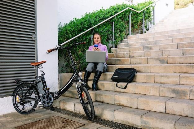 Femme d'affaires assise dans un parc avec son vélo électrique, son ordinateur portable et son téléphone portable.