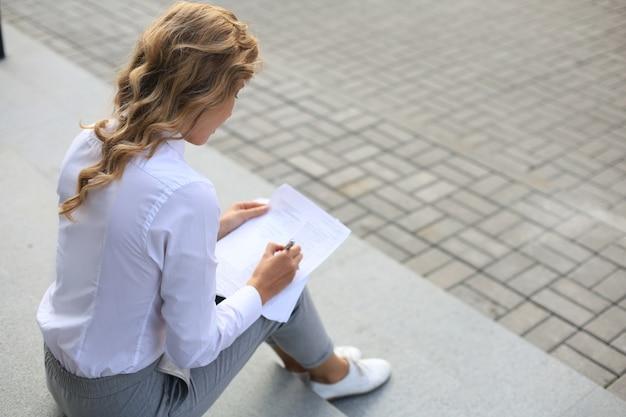 Femme d'affaires assise sur les escaliers à la recherche de documents, de graphiques et de tableaux.