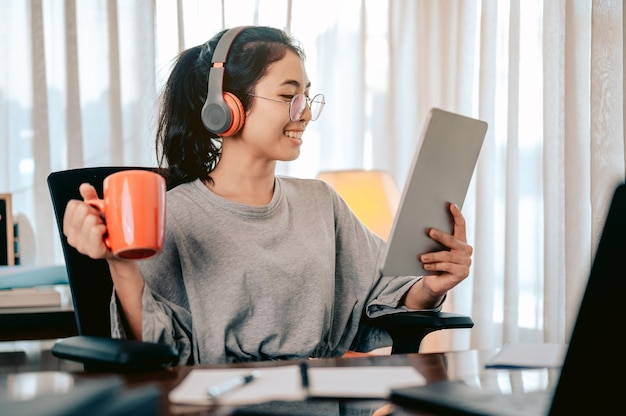 Femme d'affaires assise sur la part à la maison en train de boire du thé dans une tasse orange portant des écouteurs