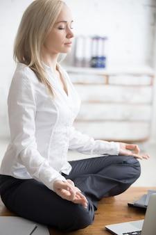 Femme d'affaires assise en pose padmasana