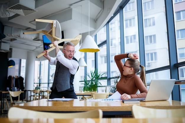 Une femme d'affaires assise à une table en bois avec un ordinateur portable et un mentor de patron d'enseignant qui travaille indique ses erreurs. crie et frappe la table avec sa main