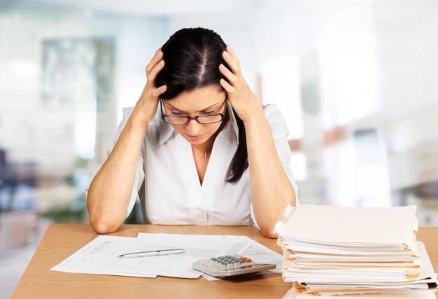Femme d'affaires assise à la table avec de nombreux papiers au bureau